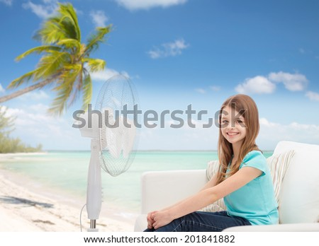 summer, weather and equipment concept - smiling little girl sitting on sofa with big fan at home - stock photo