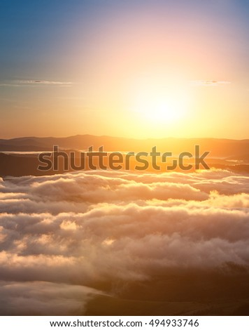Summer weather phenomenon. Seasonal landscape with morning fog in valley. Clouds drenched valley below the level of the mountains. Sunrise over creeping clouds. Sunrise over creeping clouds.