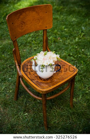 Summer wedding party festive decor, lovely fresh bouquet of white summer roses and freesias in vintage enamel tea pot on an old brown wooden chair. Retro style outdoor decoration, grass background.