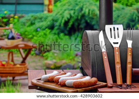 Summer Weekend BBQ Scene With Charcoal Grill On The Backyard Lawn And Outdoor Wooden Furniture In The Background