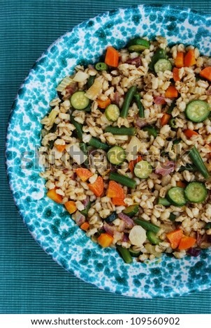 Summer whole barley salad with colorful vegetables in a green bowl - stock photo