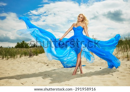 Summer woman in a blue dress on the beach - stock photo