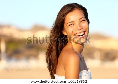 Summer woman portrait. Asian girl smiling happy laughing on beach vacation enjoying warm sunshine. Gorgeous mixed race Asian Chinese / Caucasian female model outside. - stock photo