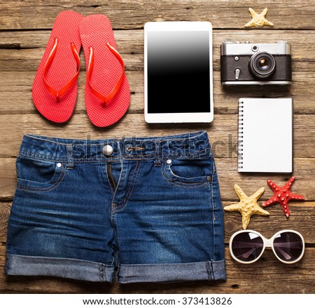 Summer women's accessories: red step-ins, denim shorts, tablet, camera, sunglasses on  wood background.