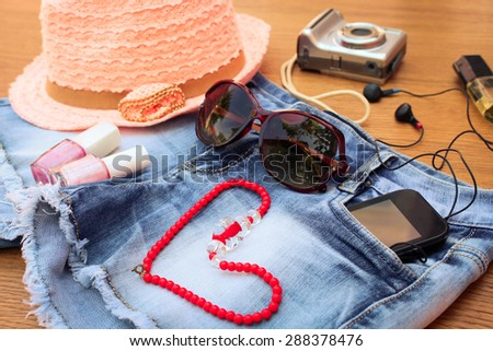 Summer women's accessories: red sunglasses, beads, denim shorts, mobile phone, headphones, a sun hat, camera, nail polish, perfum. Toned image  - stock photo