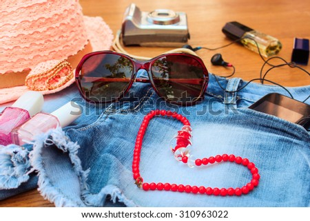 Summer women's accessories: red sunglasses, beads, denim shorts, mobile phone, headphones, a sun hat, camera, nail polish, open lipstick, perfum,. Toned image  - stock photo