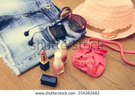 Summer women's accessories: sunglasses, beads, denim shorts, mobile phone, headphones, a sun hat, handbag, lipstick, nail polish. Toned image  - stock photo