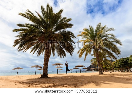 Summer yoga session on beautiful de Las Teresitas beach with gold sand brought from Sahara desert - tropical Tenerife island, Canary in Spain. Vriksha-asana, tree pose