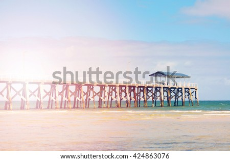 Summertime cooncept with long jetty pier and calm seas on sunny day, with added sun flare and retro style filters.  - stock photo