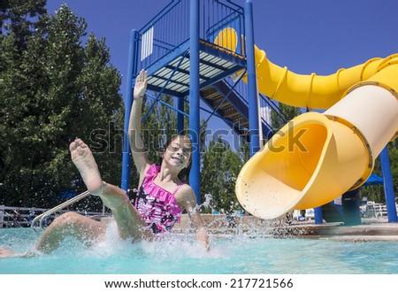 Summertime fun at the water park girl splashing on the slide - stock photo