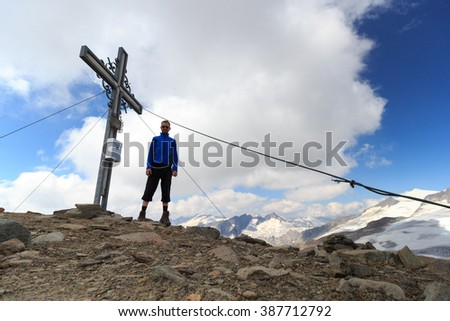 Summit cross and male mountaineer on mountain Weissspitze with panorama in Hohe Tauern Alps, Austria
