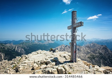 Summit Cross on High Mountain Top in Allgau Alps on Sunny Day with Blue Sky with Overview of Mountain Ranges in Distance, Near Germany-Austria Border - stock photo