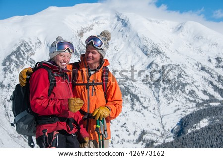 Summit Love a 20's couple happily enjoying a winter peak while backcountry skiing