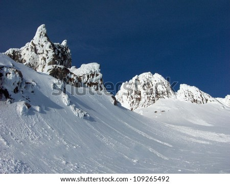 Summit of Mt. Hood in the State of Oregon, high mountain peaks with black rocks, jagged formations, snow covered hills and blue sky. - stock photo