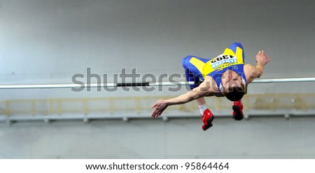 SUMY, UKRAINE - FEB.17: Shapoval Viktor wins high jump with 2.23 during the Ukainian Track and Field Championships on February 17, 2012 in Sumy, Ukraine. - stock photo