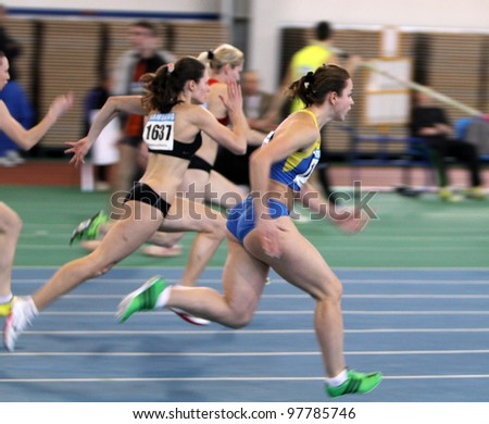 SUMY, UKRAINE - FEB.17: Unidentified girls on the 60 meters dash during the Ukrainian Track and Field Championships on February 17, 2012 in Sumy, Ukraine. - stock photo