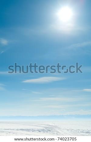 sun above frozen lake in winter - stock photo