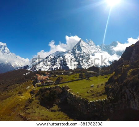 Sun above mountains peaks and green valley. Green fields and a village in rural area, a cow on field. Sunny day in the mountains. Idyllic landscape in Himalaya mountains. Himalayan mountain in summer. - stock photo
