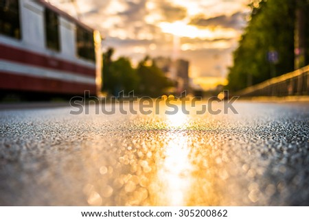 Sun after the rain in the city, the tram on the way, the view from the road level - stock photo