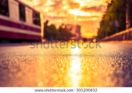 Sun after the rain in the city, the tram on the way, the view from the road level. Image in the yellow-purple toning - stock photo