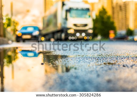 Sun after the rain in the city, view of the approaching truck with a level of puddles on the pavement - stock photo