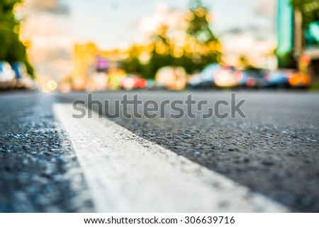 Sun after the rain in the city, view of the headlights of the approaching cars with the level dividing line - stock photo