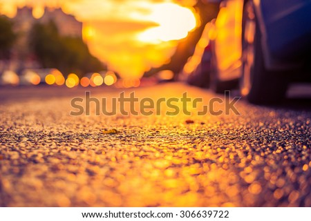 Sun after the rain in the city, view of the headlights of the approaching cars with the road level. Image in the yellow-purple toning - stock photo