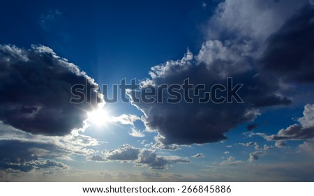 Sun and clouds on a blue sky - stock photo