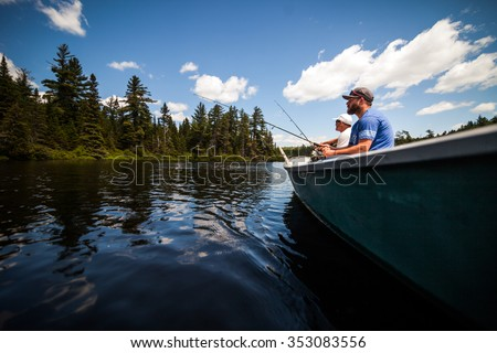 Sun and Father Fishing in a Calm Lake in Wild Nature from a Boat. - stock photo