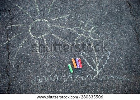 Sun and flower drawn to asphalt with colorful street chalk - stock photo