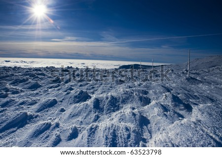 Sun and snow in mountains - stock photo