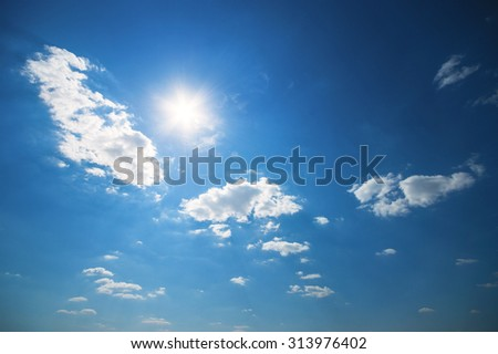 Sun and some clouds in a blue sky - stock photo