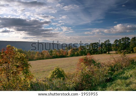 Sun-Bathed Field and Lake in Autumn - stock photo