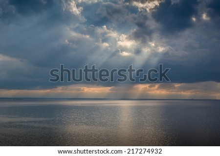 Sun beam through heavy sky over calm Mediterranean sea. Sicily coast, Italy - stock photo