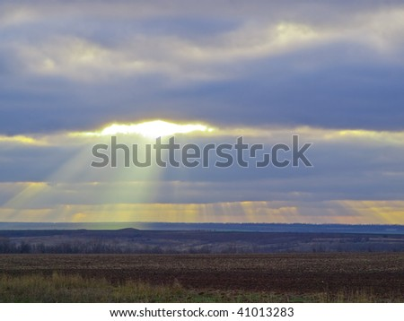 Sun beams drop on the dark earth - stock photo