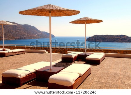 Sun beds and umbrellas on terrace in a luxury summer resort with Mediterranean sea view (Crete, Greece). - stock photo