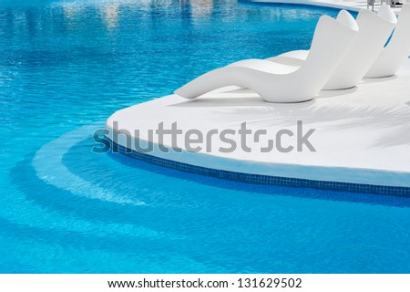 Sun-beds near a swimming pool to relax - stock photo