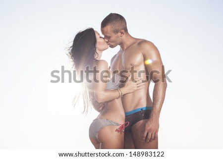 Sun bleached beautiful couple kissing on sky background - stock photo