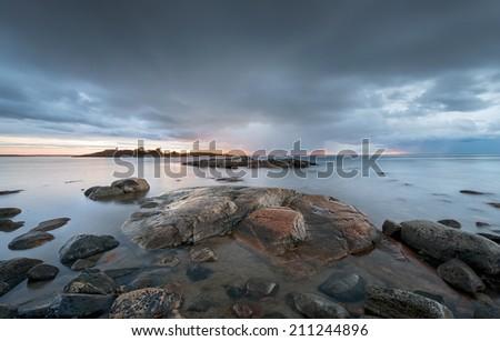 Sun breaking through the stormclouds before rain. Grisslehamn, Sweden  - stock photo