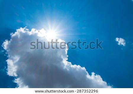 Sun burst behind cloud with dark blue sky - stock photo