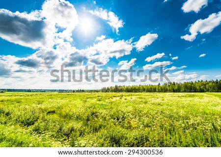 Sun comes out of cumulus clouds and illuminates a field in the village