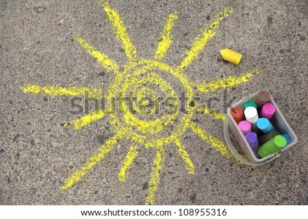 sun drawing and chalks on asphalt - stock photo