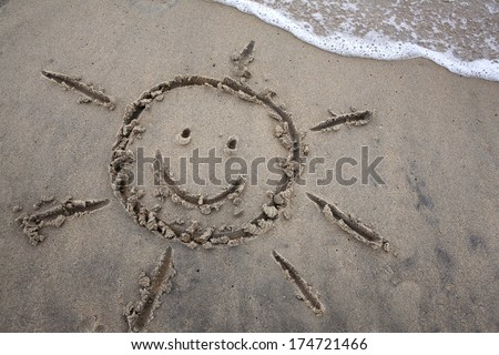 Sun drawing in the sand as waves approach, for a beach or summer vacation concept. - stock photo
