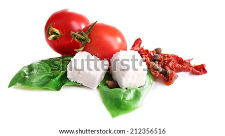 Sun dried tomatoes, feta cheese and basil leaves isolated on white - stock photo