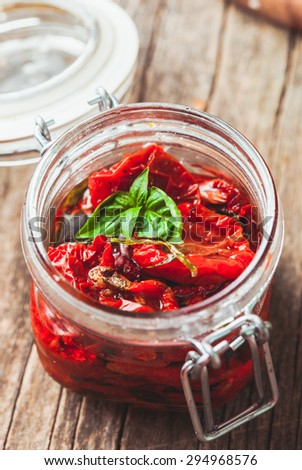 sun dried tomatoes in a glass jar with fresh basil