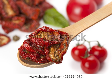 Sun dried tomatoes with basil and fresh tomatoes - stock photo