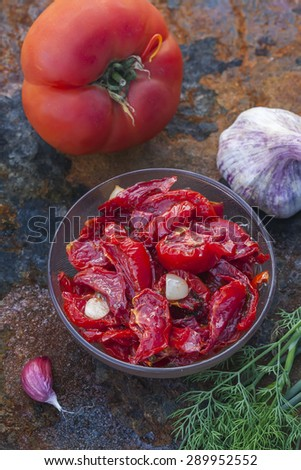 Sun dried tomatoes with olive oil  on old wooden table. Selective focus - stock photo