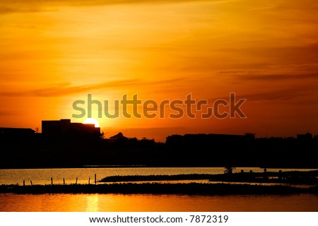 Sun drops down behind the silhouetted buildings