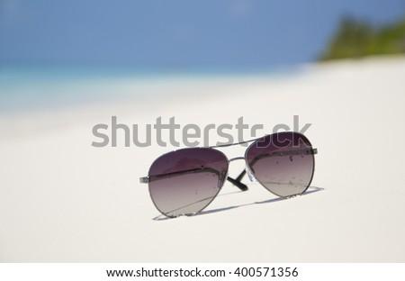 Sun glasses on a paradise tropical beach with turquoise sea, Kuredu, Maldives - stock photo