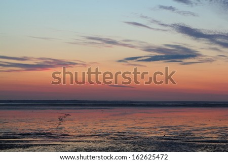 sun going down over mudflat at the german north sea coast - stock photo